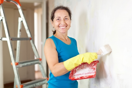 priming brush: Mature woman makes repairs in the apartment