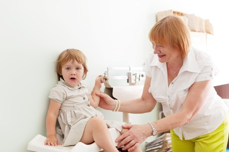 underweight: childrens doctor weighing the baby girl in clinic Stock Photo