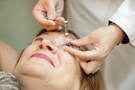 tension: Ophthalmologist measures the  ocular tension in patients Stock Photo
