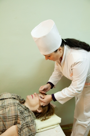 Ophthalmologist measures the eye pressure in patients photo