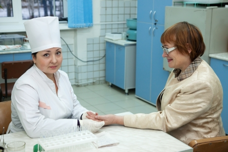 flesh surgery: Nurse taking blood sample  from patient in clinic Stock Photo