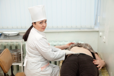 Doctor touching  stomach of patient  in clinic photo