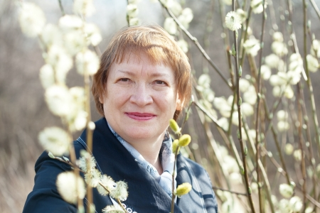 senior woman  in spring willow twig with buds outdoor photo