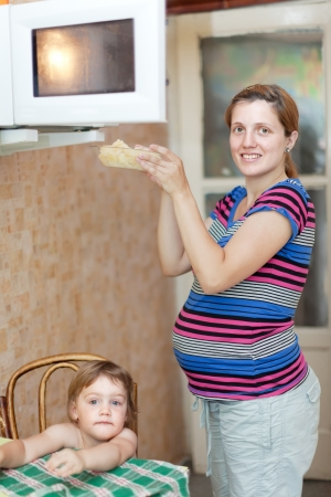 mini oven: pregnant woman warms up food in the microwave