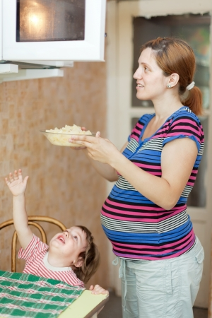 gravida: pregnant woman warms up food in the microwave