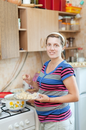 pregnant woman cooking dumplings in the pan on the stovetop photo