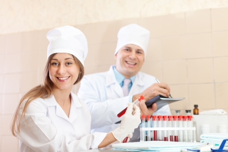 Male doctor and nurse with test tubes makes blood test in medical laboratory Stock Photo - 15978237