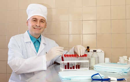 Friendly male nurse works with blood sample in medical laboratory photo
