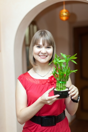 Girl with lucky bamboo plant at her home photo