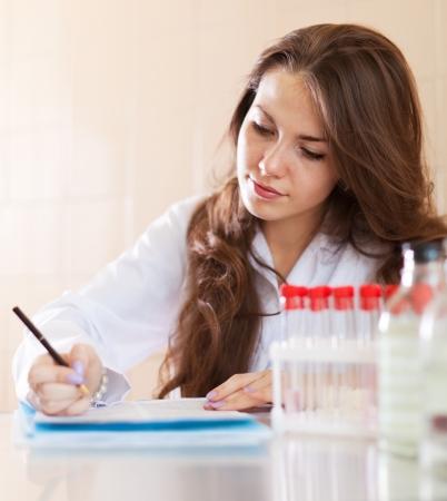 bata de laboratorio: Enfermera joven que trabaja en el laboratorio m�dico. Modelo firma la autorizaci�n de modelo
