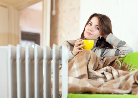 radiador: mujer con calentador de aceite amarillo taza cerca en casa