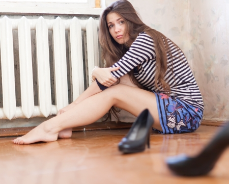 beautiful legs: Lonely girl sitting on the floor in the corner Stock Photo