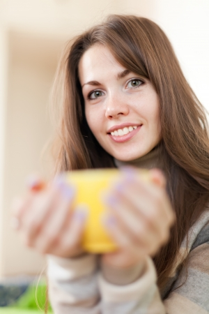 casualy: young woman with yellow cup in home