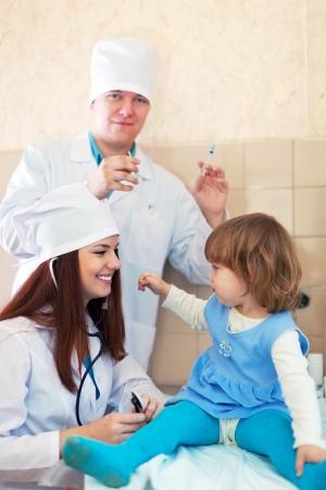 inyeccion intramuscular: Los médicos que trabajan con la niña en la clínica