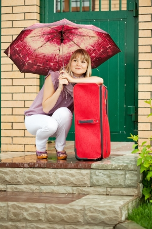 woman with luggage sitting near home door photo