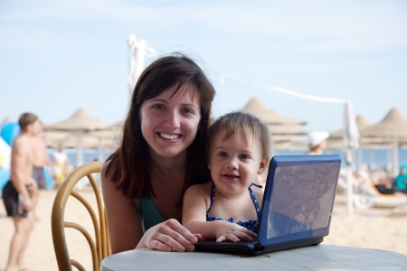 happy family  sitting  with laptop at resort beach photo