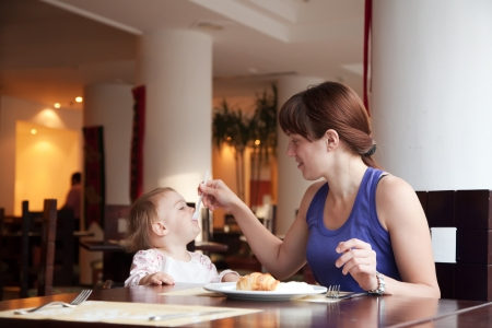 Mother feeding year-old child at cafe photo