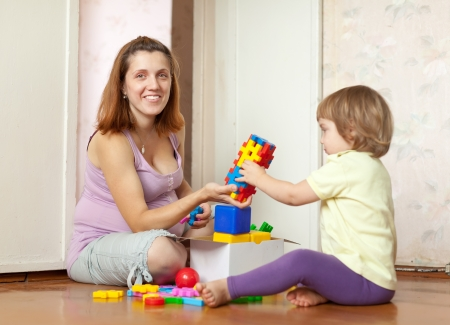 Happy mother plays with baby  in home interior photo