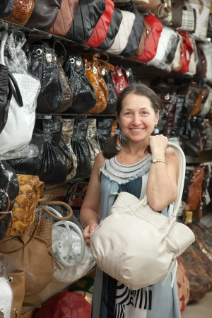 Mature woman chooses leather bag at  shop Stock Photo - 16116488