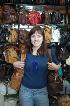 leren tas: vrouw kiest lederen tas in de winkel