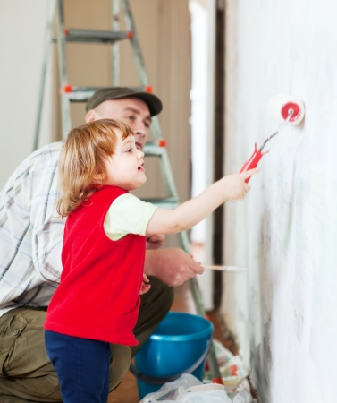 child  with father paints wall  at home photo