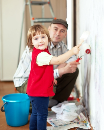 home repairs: child  with father paints wall  at home