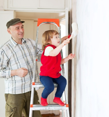 priming brush: father with child paints wall  at home Stock Photo