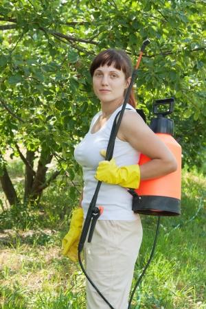Female gardener working in   yard with knapsack garden spray photo
