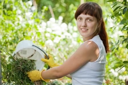 composting: Female farmer composting grass in garden