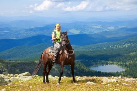 horseback riding: Female rider on horseback at mountains peak. Karakol lakes, Altai