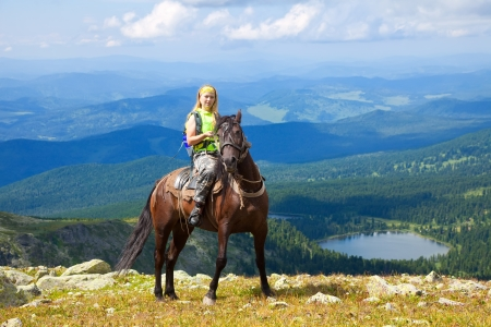 caballo jinete: Mujer jinete a caballo en el pico de las montañas. Karakol lagos, Altai