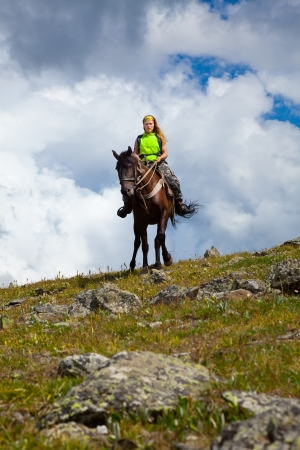 Female rider on horseback at mountains photo