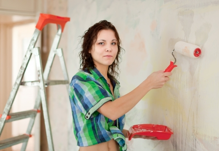 woman paints wall with roller at home Stock Photo