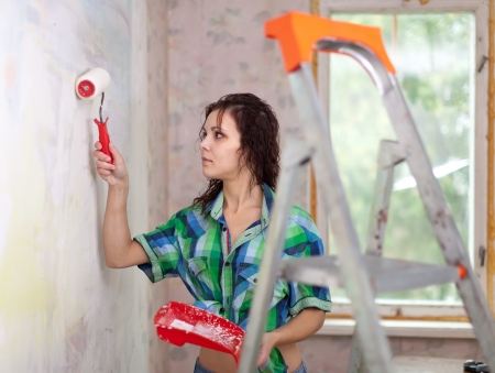 priming brush:  woman paints wall with roller at home Stock Photo