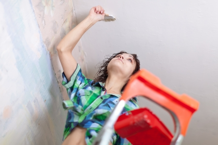 priming brush:  girl paints ceiling with brush at home