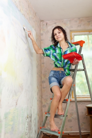 Happy girl paints wall with brush at home photo
