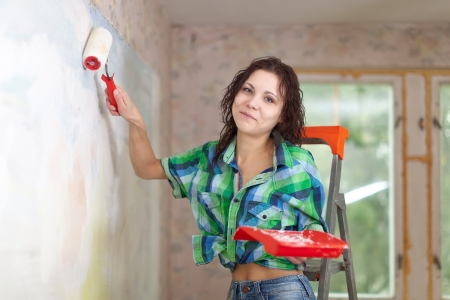 modifying: Happy woman paints wall with roller at home