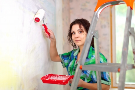 woman paints wall with roller at home photo