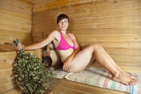 young brunette woman sitting in sauna photo