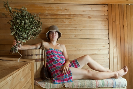 Happy girl sitting on wooden bench in sauna photo