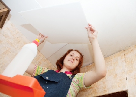 soffit cladding: Girl glues ceiling tile at home