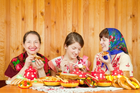 banket: Happy mother with  daughters eating pancake with caviare during  Maslenitsa festival Stock Photo