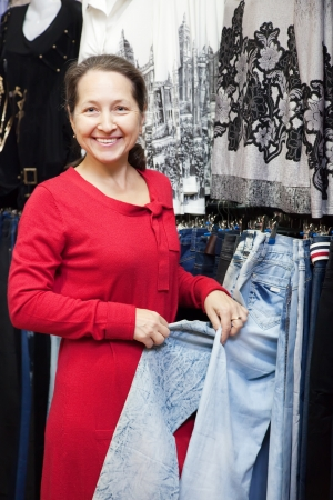 Mature woman  chooses jeans at fashionable shop photo