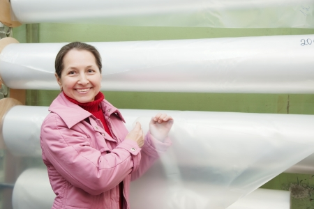 Woman  chooses polythene at foil roll at market photo
