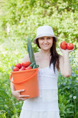 average age: Happy woman with vegetables harvest in garden