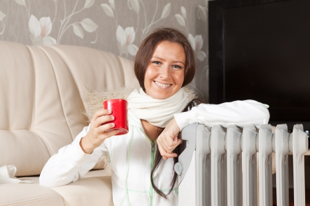 smiling woman   near warm radiator  in home photo