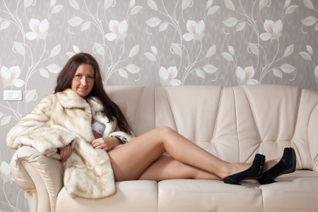furskin: woman in a fur coat sitting on the couch at home Stock Photo