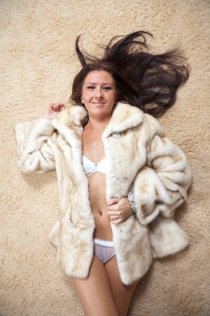 Sexy woman in fur coat laying over  rug photo