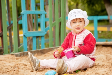 two-year child playing with sand in sandbox photo