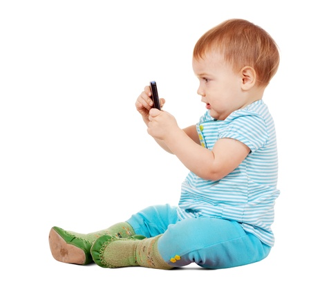 Toddler using mobile phone over white background photo